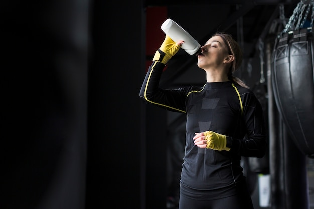 Vista lateral del boxeador hembra bebiendo agua del matraz