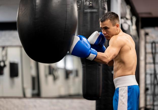 Vista lateral del boxeador masculino sin camisa practicando