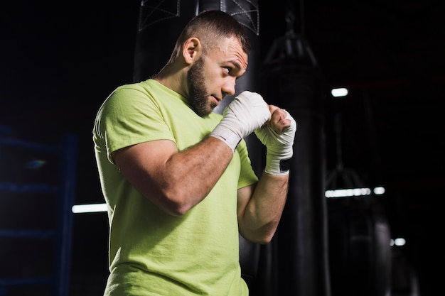 Vista lateral del boxeador masculino en camiseta practicando en el gimnasio