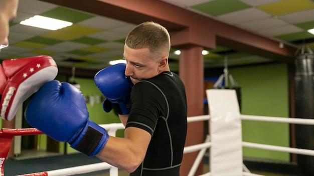 Vista lateral del boxeador masculino con entrenador haciendo ejercicio junto al anillo