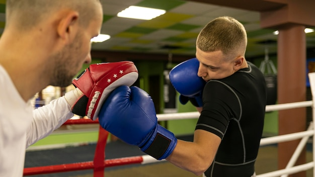 Vista lateral del boxeador masculino con entrenador junto al anillo