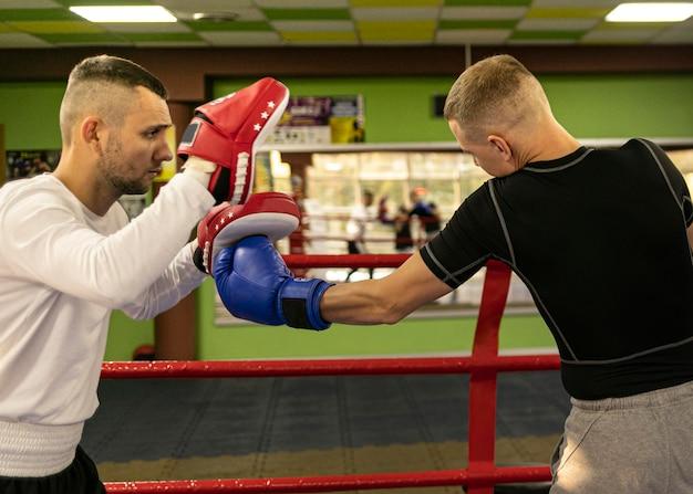 Vista lateral del boxeador masculino con entrenador