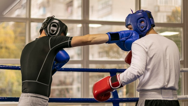 Vista lateral del boxeador masculino con guantes y casco de entrenamiento en el ring