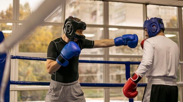 Vista lateral del boxeador masculino con guantes y casco en el ring con entrenador