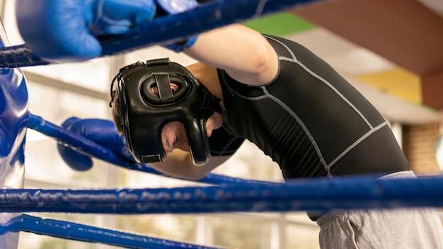 Vista lateral del boxeador masculino con guantes y casco