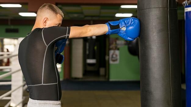 Vista lateral del boxeador masculino con guantes de entrenamiento