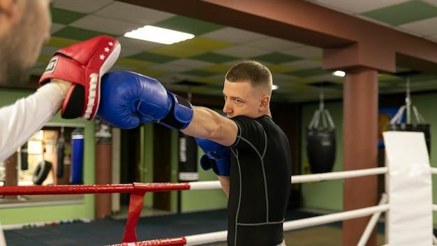 Vista lateral del boxeador masculino con guantes haciendo ejercicio con entrenador