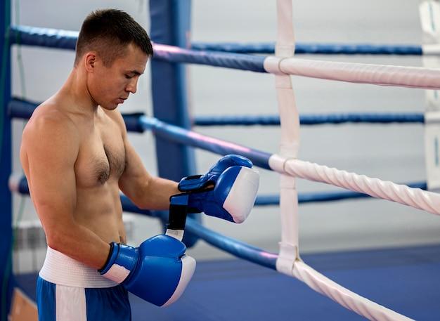 Vista lateral del boxeador masculino junto al ring