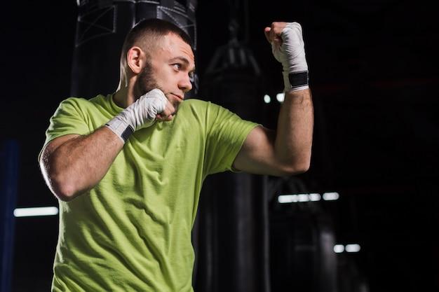 Vista lateral del boxeador masculino posando en el gimnasio.