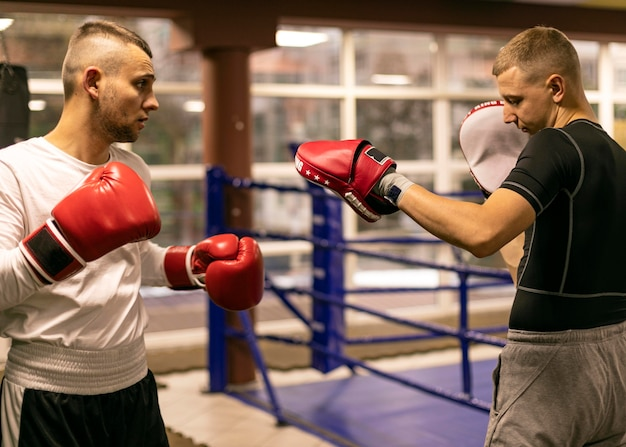 Vista lateral del boxeador masculino practicando con entrenador