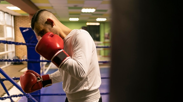 Vista lateral del boxeador masculino practicando con saco de boxeo en el ring