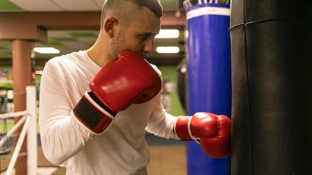 Vista lateral del boxeador masculino practicando con saco de boxeo