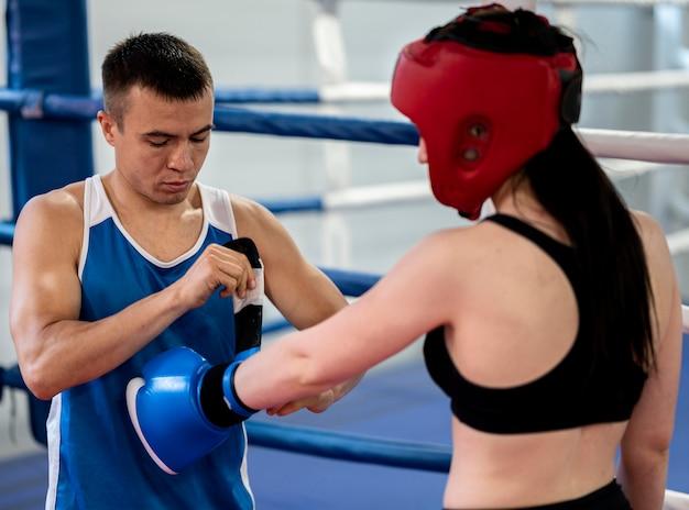 Vista lateral de la boxeadora preparándose para el entrenamiento