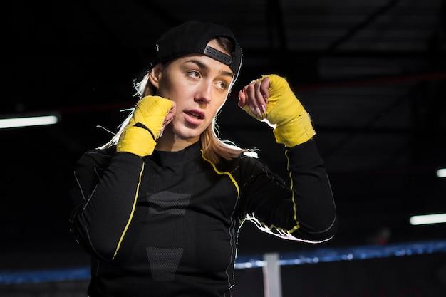 Vista lateral de la boxeadora en el ring con guantes protectores