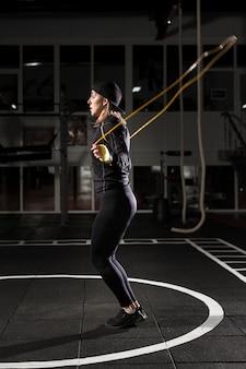 Vista lateral de la boxeadora saltando la cuerda