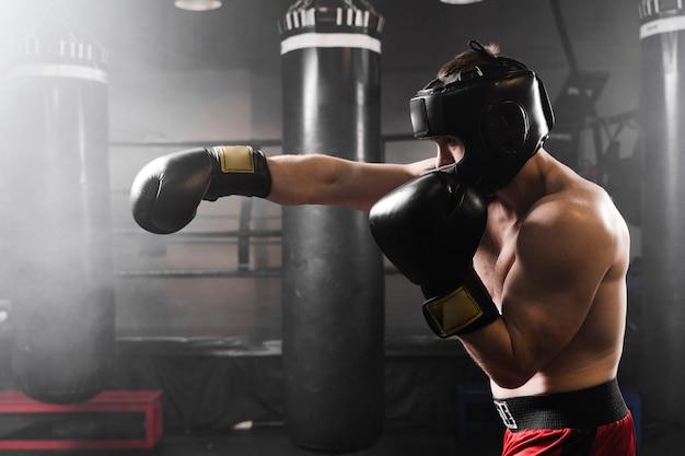 Vista lateral boxer con guantes negros de entrenamiento
