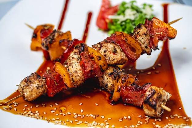 Vista lateral brochetas de pollo filete de pollo a la parrilla con pimientos rojos y amarillos salsa de condimento y semillas de sésamo en un plato