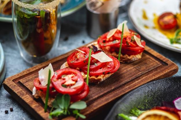 Vista lateral bruschetta con tomate albahaca cebolleta y parmesano en un tablero