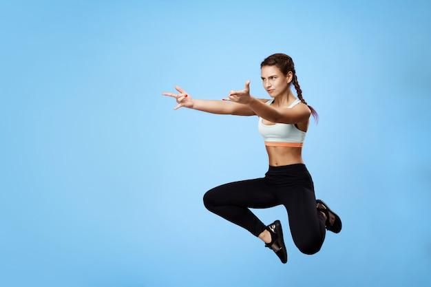 Vista lateral de buena mujer deportiva burlándose mientras entrena