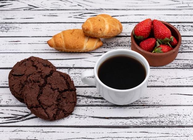 Vista lateral de café con galletas y cruasanes con fresa en superficie de madera blanca horizontal