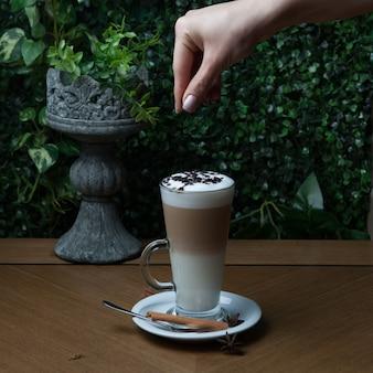 Vista lateral de café con leche con canela y chispas de chocolate y mano humana en vaso de vidrio