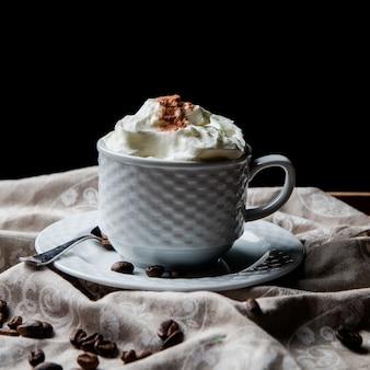 Vista lateral de café con leche con granos de café y cuchara en taza blanca