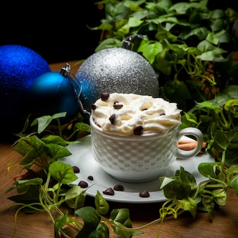 Vista lateral de café con leche con granos de café y rama de uva y bola de navidad en copa