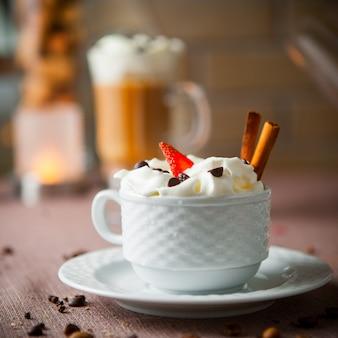 Vista lateral de café con leche con granos de café y velas en la taza blanca