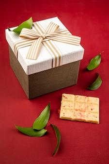 Vista lateral de una caja de regalo atada con lazo y barra de chocolate blanco sobre mesa roja