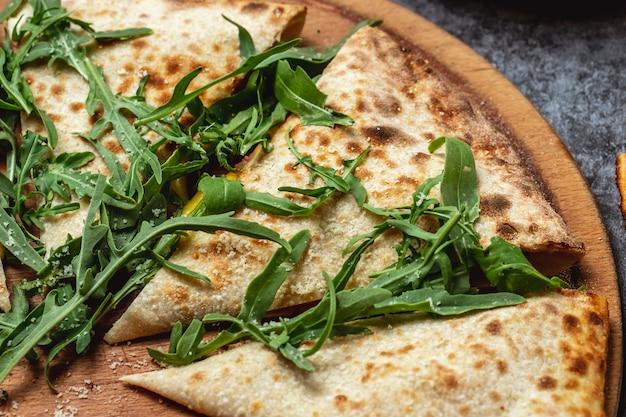 Vista lateral calzone pizza queso derretido parmesano y rúcula sobre la mesa