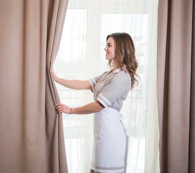 Vista lateral de una camarera joven sonriente que ajusta las cortinas en el cuarto