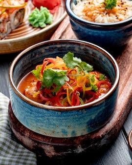 Vista lateral de camarones fritos con verduras y salsa picante en un recipiente sobre superficie rústica