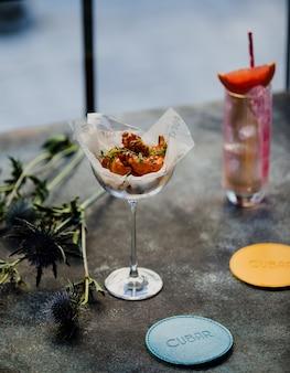 Vista lateral de camarones con salsa y hierbas en un florero de vidrio sobre una mesajpg