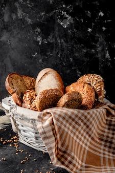 Vista lateral de la canasta llena de panes como bagel baguette centeno sobre superficie negra y superficie negra