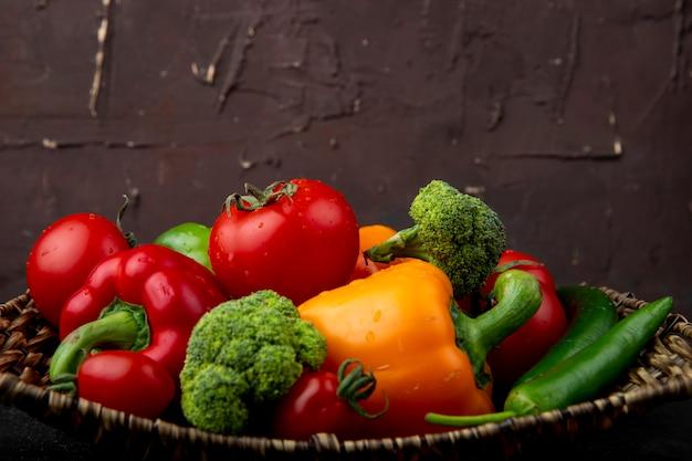 Vista lateral de la canasta llena de verduras como pimientos brócoli y tomates en superficie negra y granate