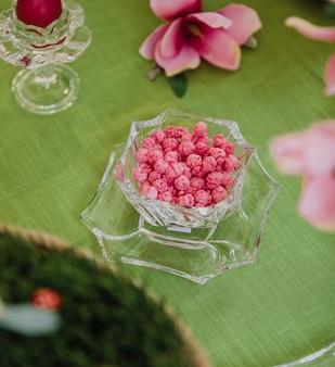 Vista lateral de caramelos de azúcar rosa en un florero de vidrio sobre la mesa verde