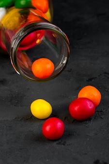 Vista lateral de caramelos de colores dispersos de la botella de vidrio en negro
