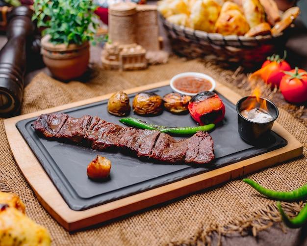 Vista lateral de carne asada langet con papas y verduras a la parrilla con salsas