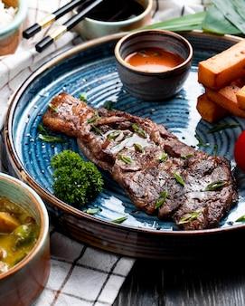 Vista lateral de carne asada con salsa picante y tomate a la parrilla con palitos de pan frito en un plato