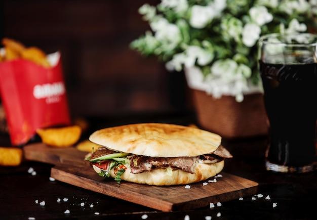 Vista lateral de carne doner kebab en pan de pita y sobre tabla de madera