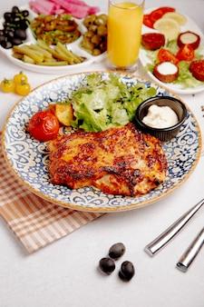 Vista lateral de carne de pollo al horno con queso, papas a la parrilla y tomates