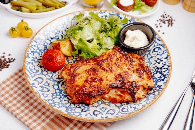 Vista lateral de carne de pollo al horno con queso tomate a la parrilla y papas