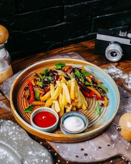 Vista lateral de carne de res a la parrilla con verduras servidas con papas fritas y salsas en placa