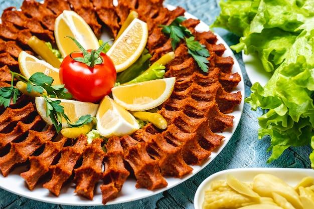 Vista lateral de carne vegetariana tartar bolas con rodajas de limón y tomate fresco en un plato