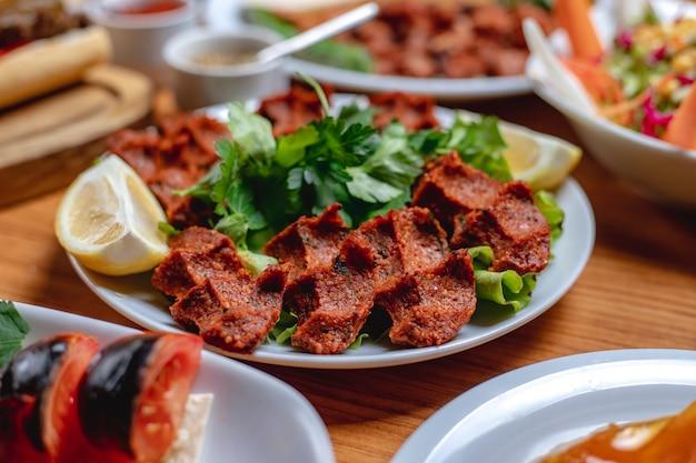 Vista lateral de carne vegetariana tartar bolas con verduras y rodajas de limón en un plato