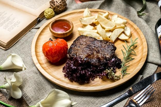 Vista lateral de carnes rojas a la parrilla con patatas en una salsa de tomate rural y romero en un tablero