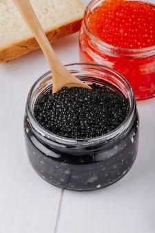 Vista lateral de caviar negro y rojo en frascos de vidrio con una cuchara