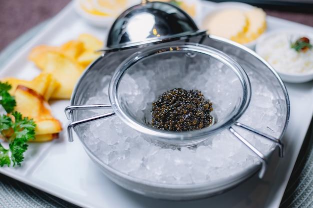 Vista lateral de caviar negro en una taza con hielo