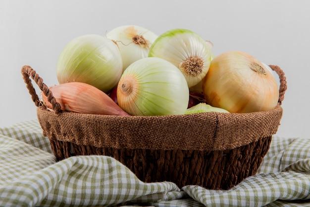 Vista lateral de las cebollas en la cesta sobre tela escocesa sobre fondo blanco.