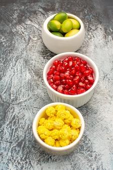 Vista lateral de cerca dulces cuencos blancos de frutas cítricas semillas de granada y caramelos amarillos